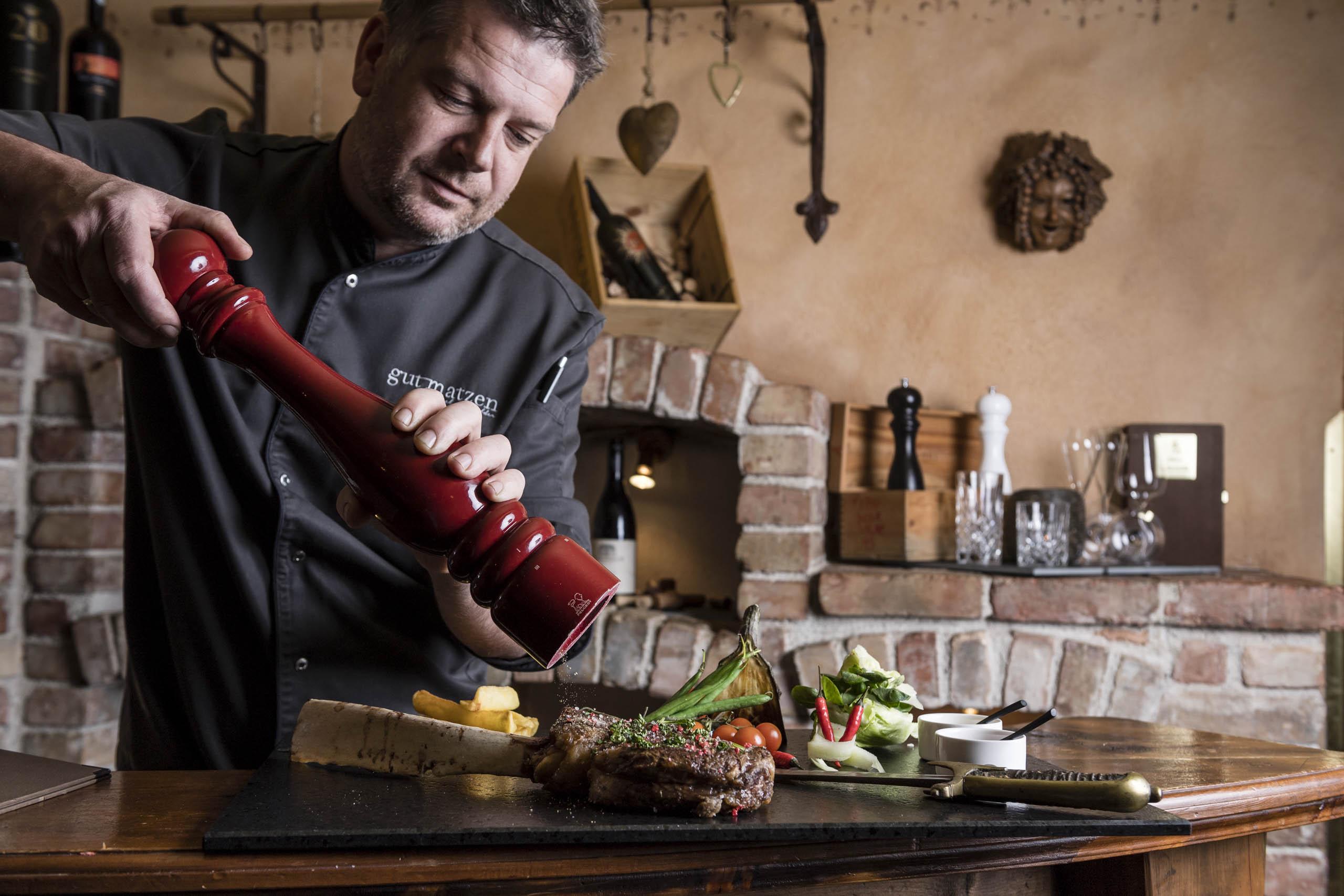Der Chef würzt das bereits angerichtete Steak